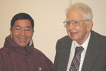 Ronald Coase greets a conference attendee