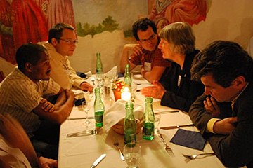 Faculty and participants talk together during dinner